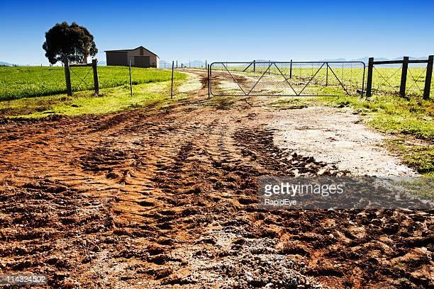 Farm gate with muddy dirt road