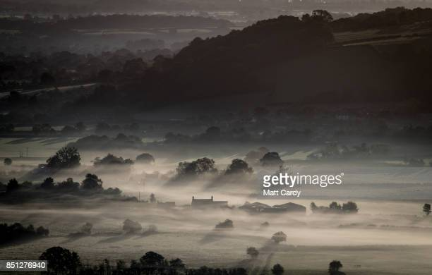 A farm house is surrounded by early morning mist lingering in fields as the autumn sun rises over the Somerset Levels as viewed from Glastonbury Tor...