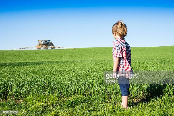 Farm kid looking at a crop sprayer