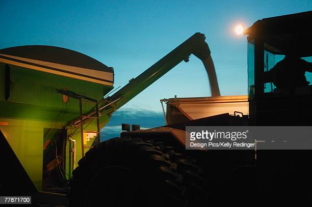 Farm machinery harvesting at night