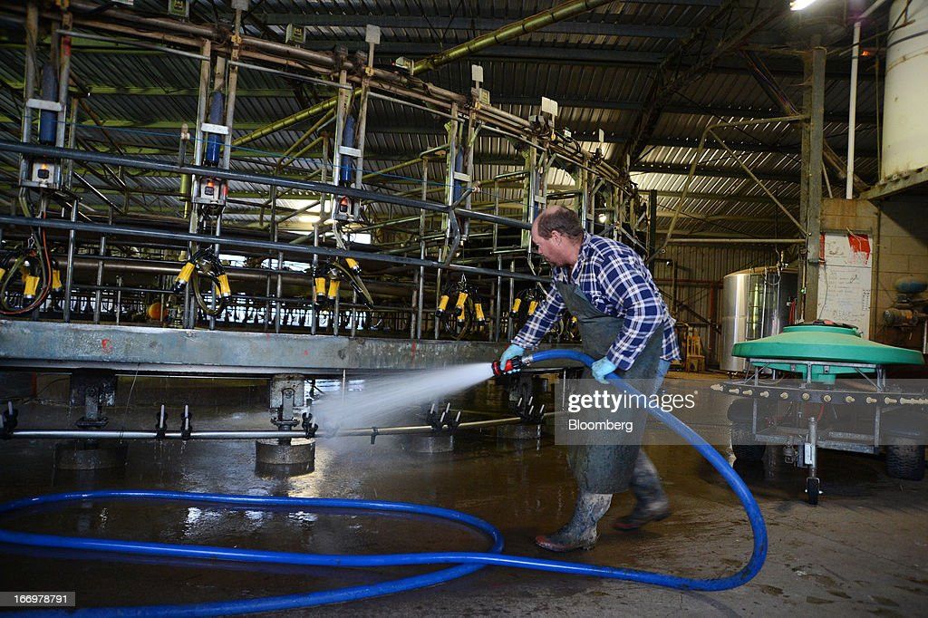 Farm manager Colin Ryan hoses down the rotary milking parlor at the end of a milking session at Pearson's Farm north of Moama, New South Wales, Australia, on Thursday, April 18, 2013. Farmers in Australia's A$4 billion ($4 billion) dairy industry are striking direct deals with supermarkets that control 80 percent of the country's grocery sector, as a drive to sell milk for A$1 a liter ($3.92 a gallon) squeezes profits. Photographer: Carla Gottgens/Bloomberg via Getty Images