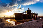 Farm oil storage tanks surrounded by water after rain with stormy sunset and sunflare. Metaphor: sun setting on oil production.  Horizontal, copy space, no people, names or logos.