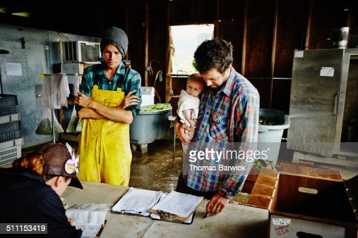 Farm owner holding infant looking over log
