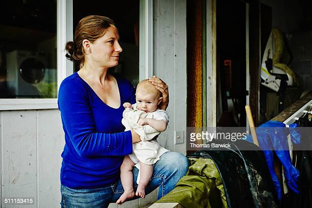 Farm owner holding infant standing in work shed
