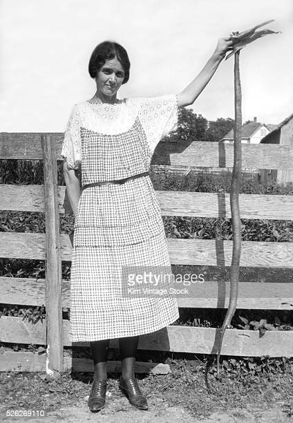 Farm woman holds a large snake by a corn shuck on her farm Snake is possibly a Blue Racer or Milk Snake