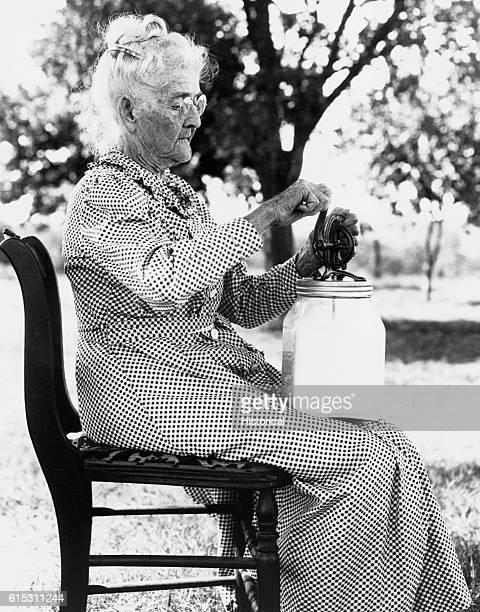 Farm woman using a small modern churn Stephens Co Oklahoma July 1935