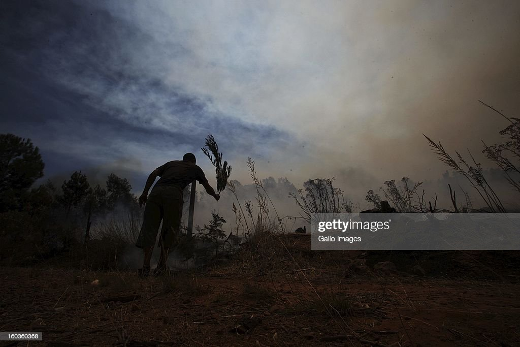 A farm worker beats flames on January 29, 2013, in Paarl, South Africa. No firemen were present as the veld fire swept through the entire Boland region in the Western Cape.
