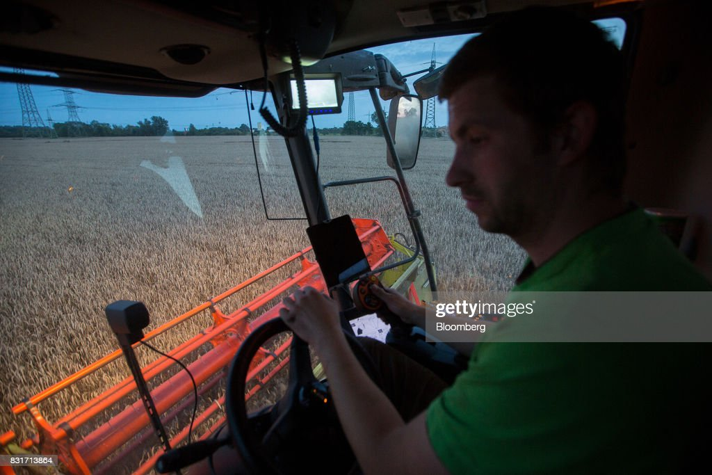 A farm worker drives a Claas KGaA combine harvester during wheat harvest in Wustermark, Germany, on Monday, Aug. 14, 2017. In Germany, problems with specific weight and Hagberg, a measure of baking quality, mean as much as 40 percent of wheat may have to go to the animal feed market this year. Photographer: Krisztian Bocsi/Bloomberg via Getty Images