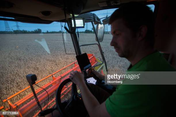 A farm worker drives a Claas KGaA combine harvester during wheat harvest in Wustermark Germany on Monday Aug 14 2017 In Germany problems with...