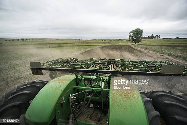 A farm worker drives a John Deere Co tractor while ploughing a field for the replanting of maize caused by drought in Mpumalanga South Africa on...