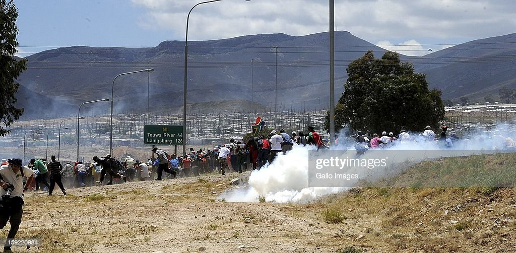 Farm workers at the N1 highway De Doorns on January 9, 2013, in Cape Town, South Africa. The farm workers shut down the N1 by lighting tires on fire and placing large rocks on the road.