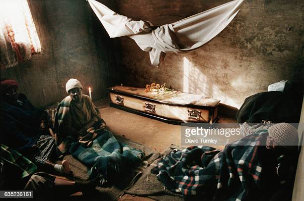 A farm worker's family keeps vigil around his coffin mourning his death in a workrelated accident