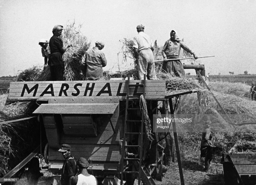 Farm workers loading hay. On the agricultural machine is a big 'Marshall' sign. The machines were part of the Marshall Plan for Austria. Photography. 1947. (Photo by Imagno/Getty Images) [Landwirtschaftliche Betriebe der Stadt Wien im Rahmen des Marshall-Plans. oesterreich. Photographie. 1947.]
