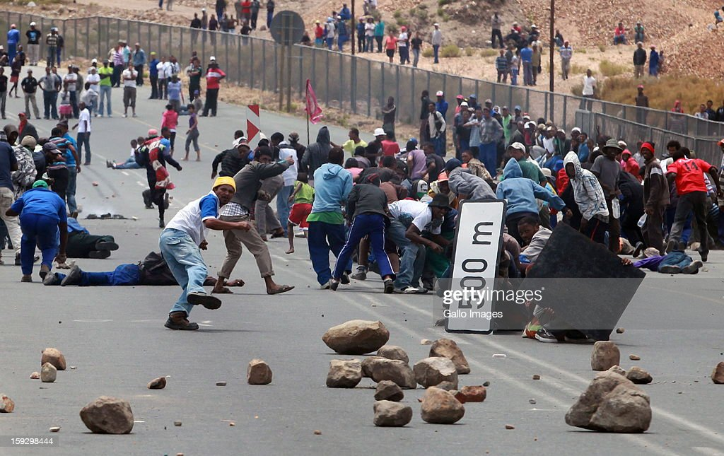 Farm workers scatter as police fire rubber bullets to stop them making barricades to block off the N2 on January 10, 2013 in Grabouw, South Africa. Seasonal farm workers are striking over wage disputes.
