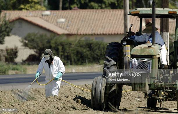 Farm workers spray chemicals at the edge of a field bordering homes on August 12 2004 near the town of Lamont southeast of Bakersfield California...
