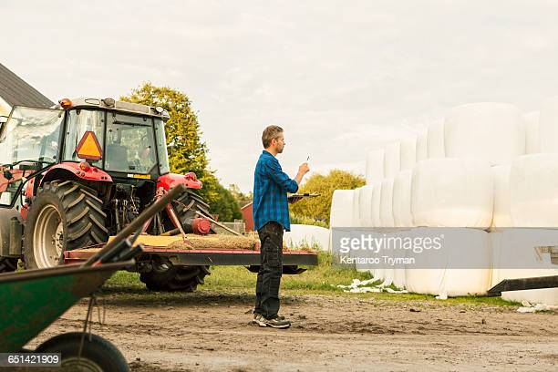 Farmer analyzing covered hay bales while standing by tractor at farm
