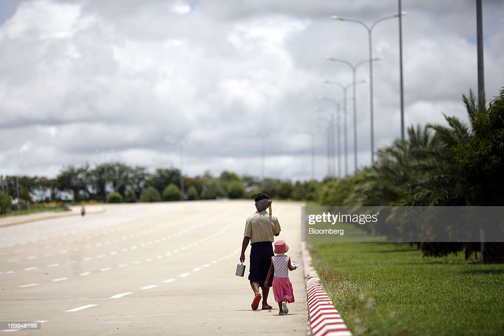 A farmer and a child walk along a highway in Naypyidaw, Myanmar, on Wednesday, June 5, 2013. Myanmar hosts the three-day World Economic Forum on East Asia starting today, with heads of state and executives from companies including General Electric Co., Coca-Cola Co. and WPP Plc attending. Photographer: Dario Pignatelli/Bloomberg via Getty Imagesd