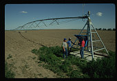 A farmer and field workers stand next to a center pivot irrigation system as they discuss other crop irrigation methods