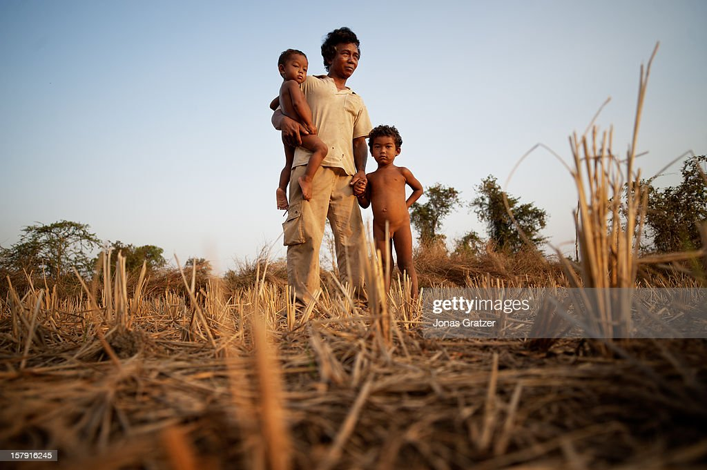 A farmer and his children stand on where used to be their farm land they have lost their land to land grabbers land grabbing has become a serious...