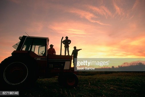 Farmer and his sons watching the sunset : Stock Photo