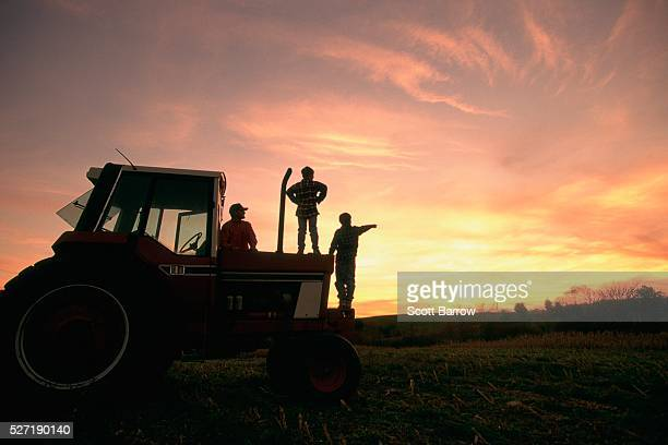 Farmer and his sons watching the sunset
