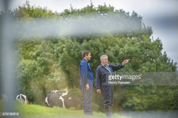 Farmer and son discussing in field