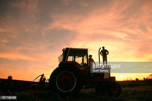 Farmer and son watching the sunset