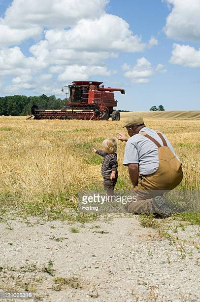 Farmer and young son with combine harvester
