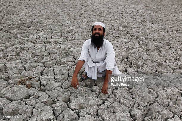 A farmer at cracked land looking to the sky hoping for monsoon rain on a hot summer in Allahabad