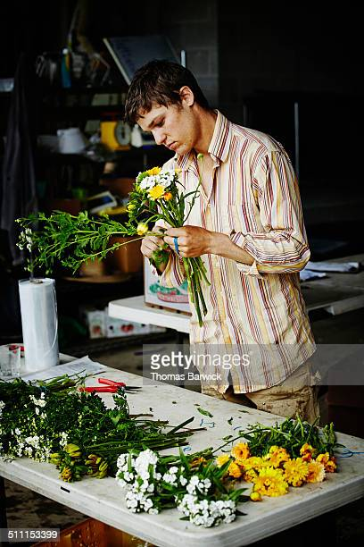 Farmer at table organizing flower bouquets