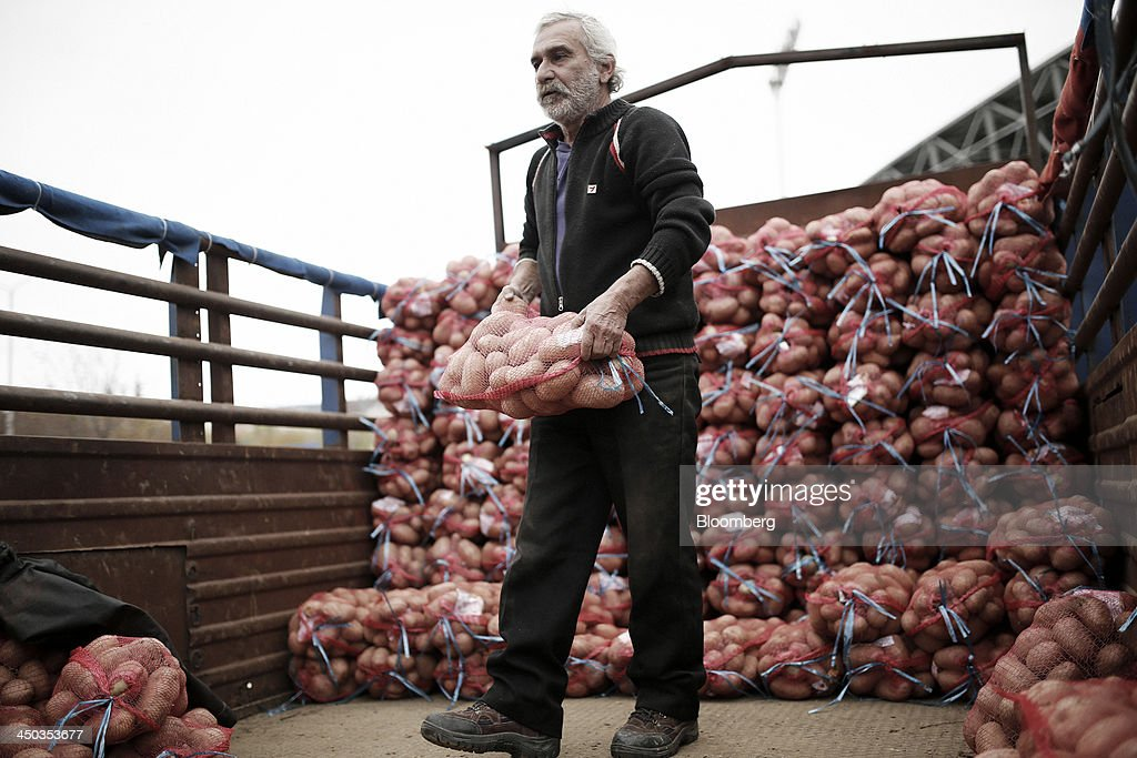 A farmer carries a sack of potatoes as he stands on the back of a truck at a farmers' market in Thessaloniki, Greece, on Saturday, Nov. 16, 2013. Greek Prime Minister Antonis Samaras, who survived a no-confidence vote on Nov. 11 with his parliamentary majority reduced to four, is trumpeting the first economic growth in seven years for 2014. Photographer: Konstantinos Tsakalidis/Bloomberg via Getty Images