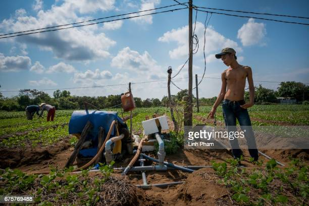 A farmer checks his water pumping machine on April 28 2017 in the South side of Thua Duc Village Binh Dai District Ben Tre Province Vietnam Due to...