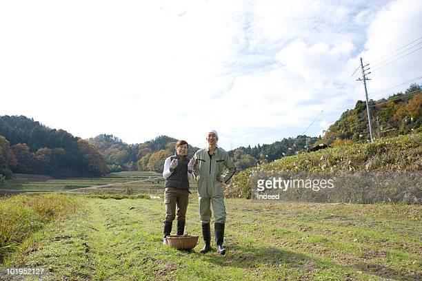 Farmer couple standing in open field, smiling