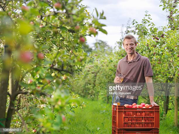 Farmer drinking cider in orchard