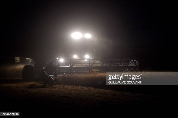 A farmer drives a combine harvester during a wheat harvest by night on July 28 2016 in Monthodon near Tours central France / AFP / GUILLAUME SOUVANT