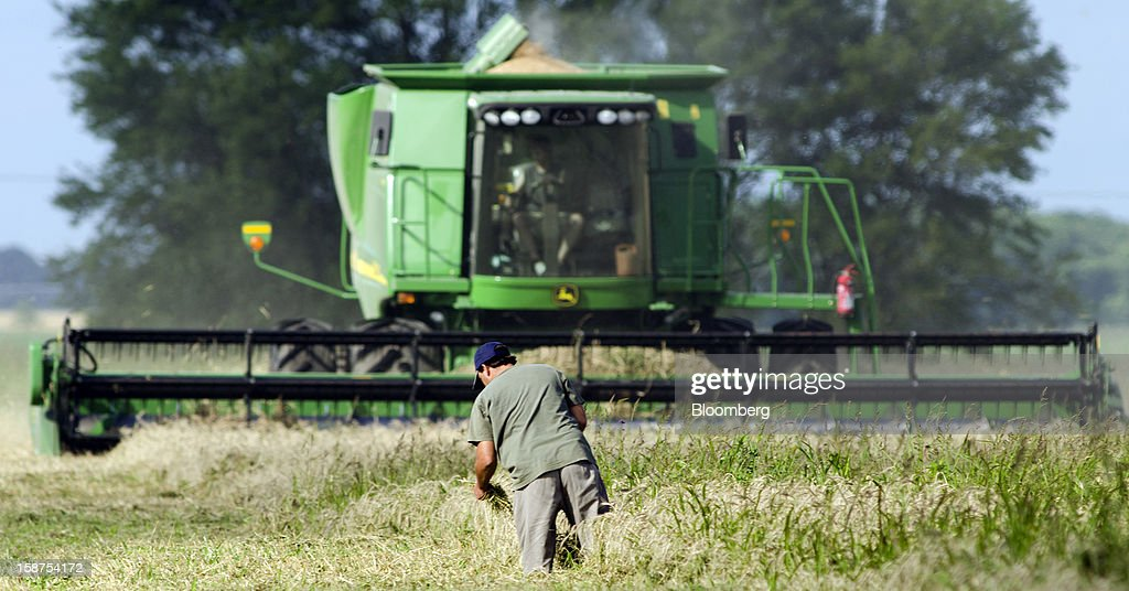 A farmer drives a John Deere combine while another man works in a field during wheat harvest near Salto, Argentina, on Monday, Dec. 24, 2012. Argentina, South America's largest wheat producer, will have a current crop as low as 9 million tons because of excess rain, heat and plant diseases, a board director of wheat producers association Aaprotrigo said. Photographer: Diego Giudice/Bloomberg via Getty Images