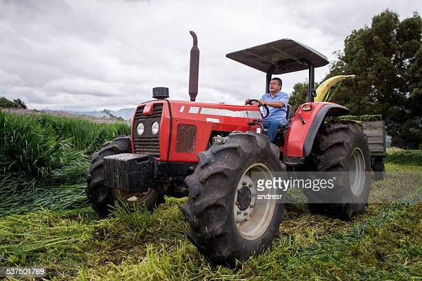 Farmer driving a tractor harvesting the land