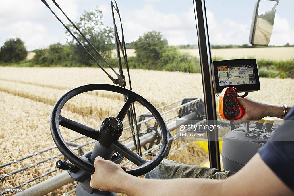 Farmer driving harvester in crop field