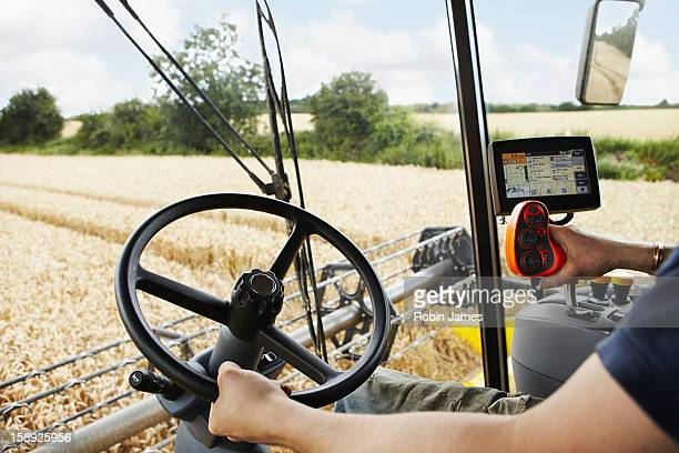Farmer driving harvester in crop field