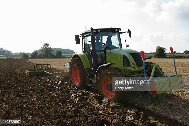 Farmer driving tractor through fields