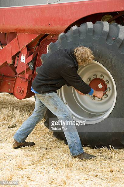 A farmer fixing the wheel of a combine