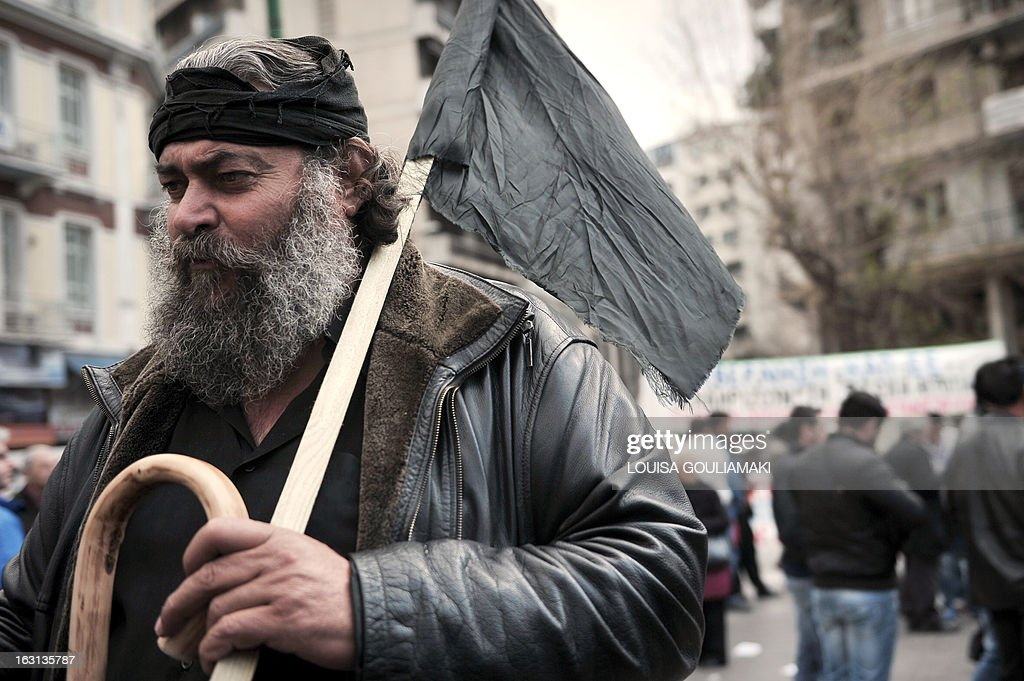 A farmer from Crete island holds a black flag during a rally by farmers' unions from all over Greece on March 5, 2013. Some 2,000 Greek farmers gathered in Athens to demand lower taxes, arguing that the rising cost of fuel and electricity was driving them to ruin.The farmers also called for subsidies from the heavily indebted state, which has been forced to undertake a tough austerity policy, to help them lower their costs and remain competitive. AFP PHOTO / LOUISA GOULIAMAKI