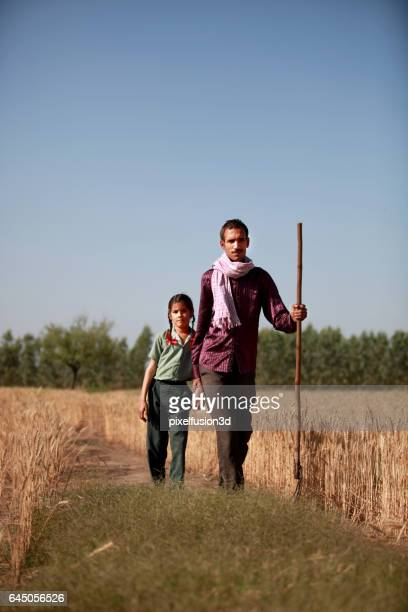 Farmer & his daughter walking in the field