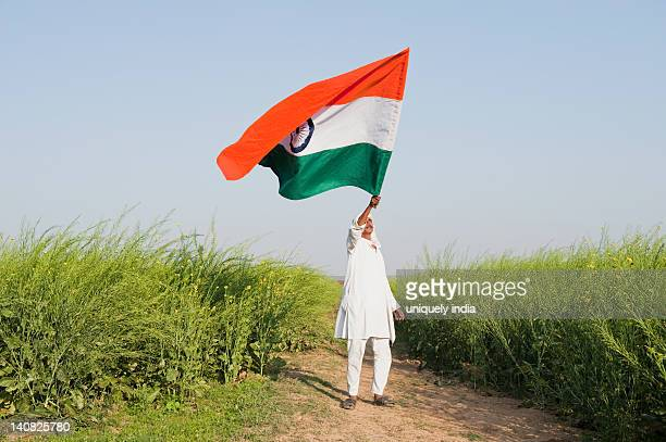 Farmer holding an Indian flag near an oilseed rape field