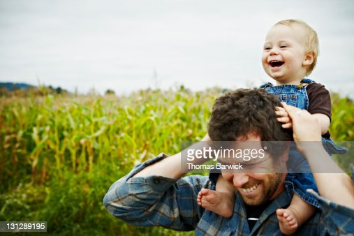 Farmer holding baby boy on shoulders laughing : Stock Photo