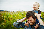 Farmer holding baby boy on shoulders laughing