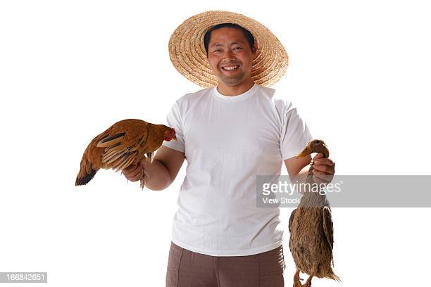 Farmer holding chicken and duck