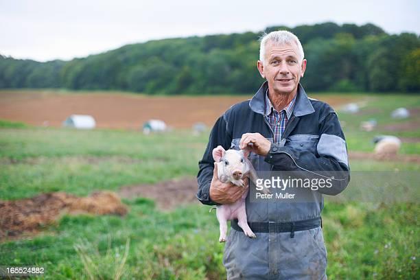 Farmer holding piglet in field