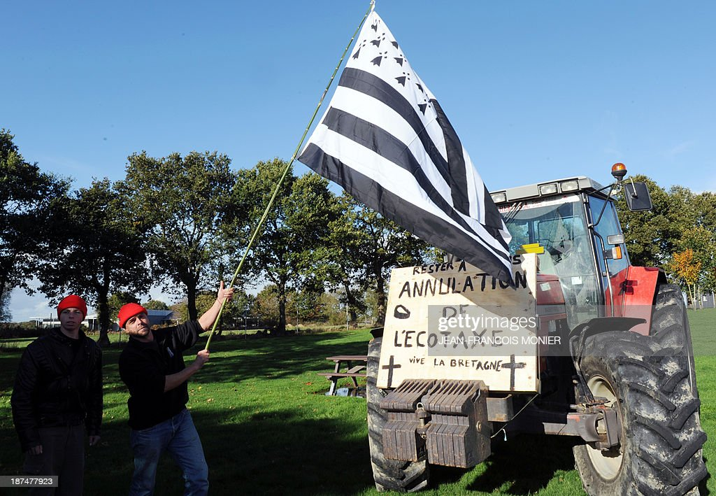 A farmer holds a Breton flag in front of a tractor with words on a placard reading 'Cancellation of the eco tax, long live Brittany' during a demonstration against jobcuts and against the government's 'Eco-tax', a controversial environmental tax on heavy goods vehicles near an 'Ecotax' control portal in Jugon-les-Lacs, western France, on November 9, 2013. The ecotax, aimed at encouraging environmentally friendly commercial transport, imposes new levies on French and foreign vehicles transporting commercial goods weighing over 3.5 tonnes but its implementation has repeatedly been put off.