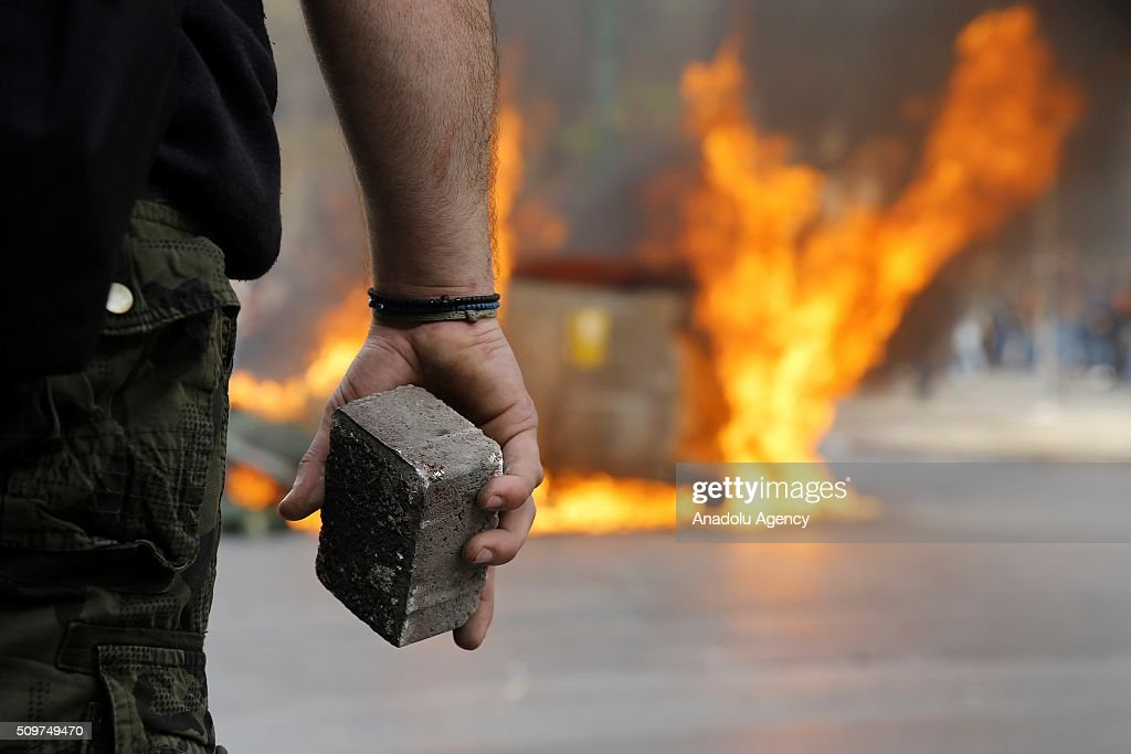A farmer holds a stone Greek farmers clash with police officers in front of the Agriculture ministry in Athens, during a demonstration against pension reform on February 12, 2016.